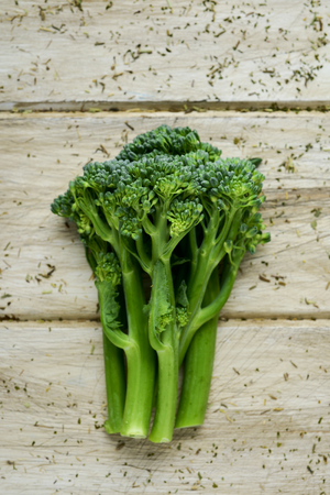 high-angle shot of some stems of broccolini on an off-white rustic wooden table Stok Fotoğraf