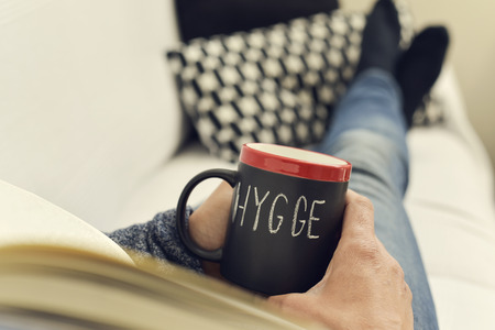 wholeness: closeup of a young man reading a book with a cup of coffee in his hand with the text hygge, a danish and norwegian word for comfort or enjoy, which can be a whole philosophy of life