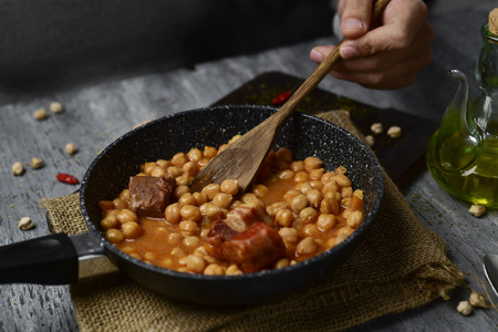 spanish home: a frying pan with potaje de garbanzos, a spanish chickpeas stew with chorizo and serrano ham, on a rustic wooden table