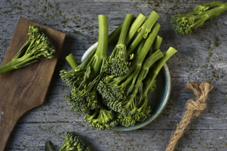 high-angle shot of some stems of broccolini in a green ceramic plate placed on a gray rustic wooden table
