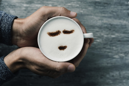 wholeness: high-angle shot of a young caucasian man holding a cup of cappuccino with a happy face drawn with cocoa powder on the milk foam, on a gray rustic table