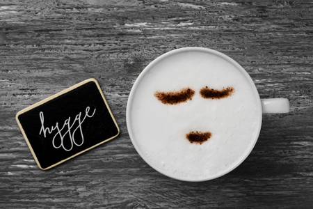 wholeness: high-angle shot of a cup of cappuccino with a happy face drawn with cocoa powder and a signboard with the text hygge, a danish and norwegian word for comfort or enjoy, a whole philosophy of life