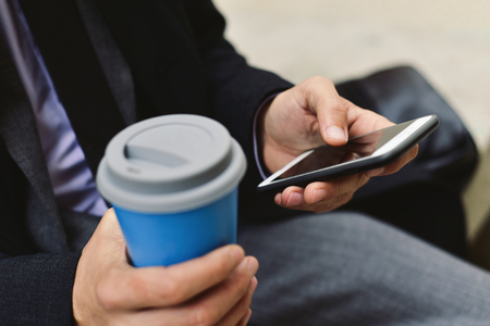 closeup of a young caucasian businessman in a gray suit and a dark gray coat with a cup of coffee in one hand and his smartphone in the other hand outdoors Stock Photo