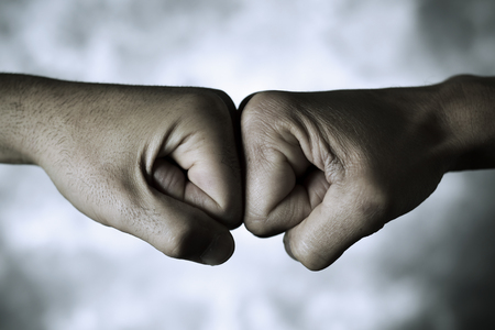 closeup of the hands of two young caucasian men who are bumping their fists