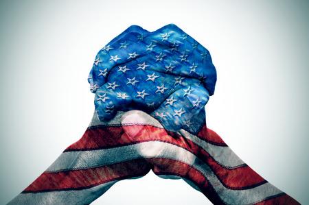 Die gefalteten Hände eines jungen kaukasischen Mannes gemustert mit der Flagge der Vereinigten Staaten auf einem off-weißen Hintergrund, mit einer Folie Vignette hinzugefügt