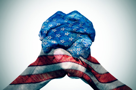 the clasped hands of a young caucasian man patterned with the flag of the United States on an off-white background, with a slide vignette added Archivio Fotografico