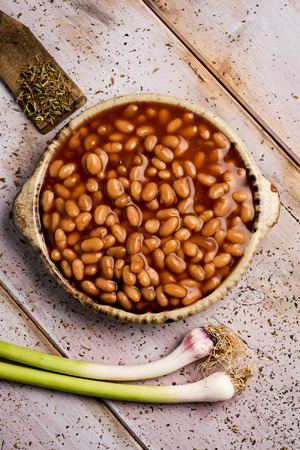 high-angle shot of an earthenware bowl full of baked beans and some green garlics on a rustic wooden table