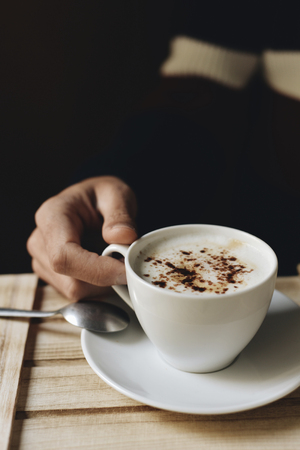 wholeness: closeup of a young caucasian man about to drink a cup of cappuccino, sitting at a rustic wooden table