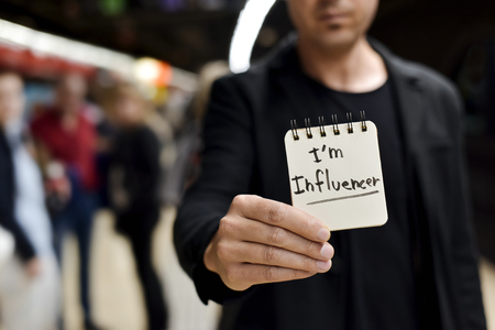 closeup of a young caucasian man in a train or metro station showing a spiral notepad with the text I am influencer written in it