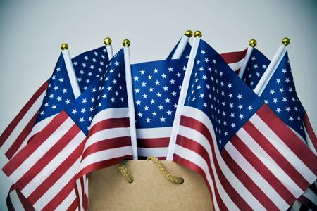 closeup of some flags of the United States in a brown paper shopping bag, with a vignette added Stock Photo