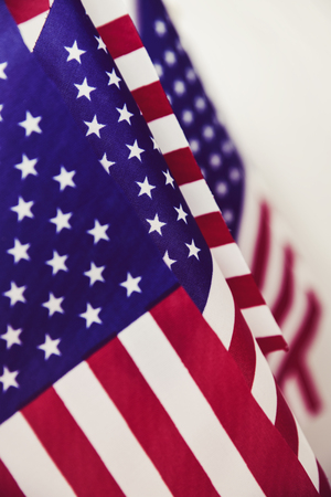 closeup of many american flags put in line, against an off-white background