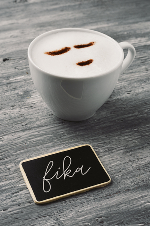 a cup of cappuccino with a happy face drawn with cocoa powder and a signboard with the text fika, a danish and finish word for have a coffee or a break with colleagues, family andor friends Фото со стока