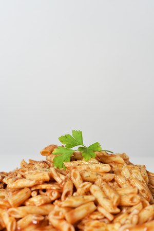 gastro: closeup of a plate with an assortment of different cooked pasta served with tomato sauce and herbs on a white table against a white background, with a blank space on top