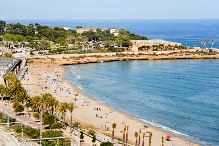 frequented: TARRAGONA, SPAIN - MAY 28, 2017: Sunbathers at Miracle Beach in Tarragona, Spain. The city, in the famous Costa Daurada area, has several urban beaches like this, frequented mostly by local
