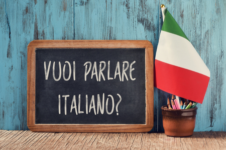 a chalkboard with the question vuoi parlare italiano?, do you want to speak Italian? written in Italian, a pot with pencils, some books and the flag of Italy on a wooden desk