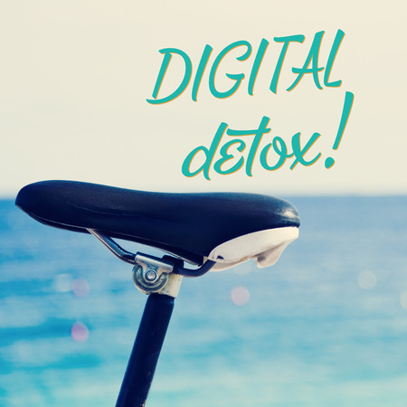 disconnecting: closeup of the saddle of a bicycle parked next to the sea and the text digital detox