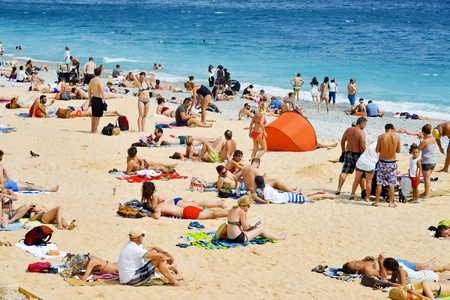 alpes maritimes: NICE, FRANCE - JUNE 4, 2017: People sunbathing on the beach in Nice, in the French Riviera, France, next to the Promenade des Anglais, the famous seafront walkway of the city