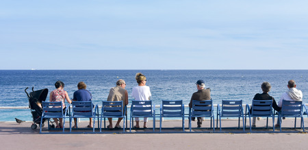 alpes maritimes: NICE, FRANCE - JUNE 4, 2017: People sitting in the characteristic blue chairs facing the Mediterranean sea at the famous Promenade des Anglais in Nice, in the French Riviera, France