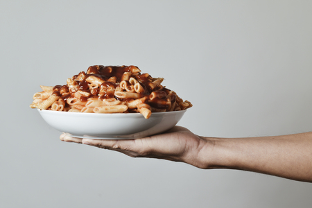 gastro: closeup of a young caucasian man holding a plate with an assortment of different cooked pasta served with tomato sauce in his hand, against an off-white background Stock Photo