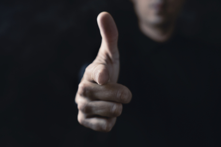 closeup of a young caucasian man pointing his forefinger to the front pretending that it is a gun, against a black background Zdjęcie Seryjne