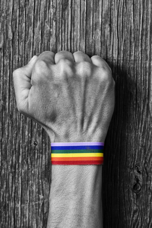 closeup of a young caucasian man in black and white with a colorful band patterned as the rainbow flag tied to his wrist and his fist raised against a rustic wooden background Stock Photo