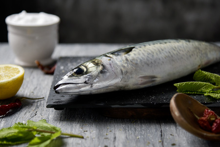 closeup of a raw fresh mackerel on a slate tray placed on a gray rustic wooden table