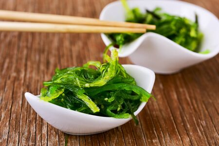 goma wakame or seaweed salad in some white ceramic bowls, on a rustic wooden table Imagens