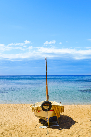 an old fishing boat stranded in the quiet beach Platja de Sa Caleta in Lloret de Mar, in the Costa Brava, Spain