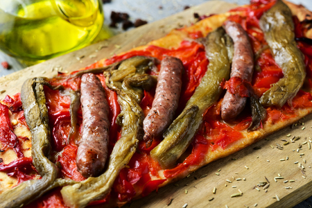 closeup of a slice of coca de recapte, a typical catalan savory cake similar to pizza, made with grilled eggplant and red pepper, and pork sausage, on a rustic wooden table