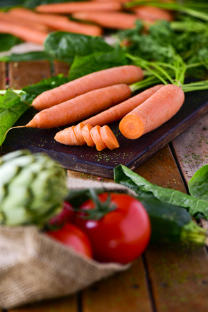 closeup of some different raw vegetables, such as tomatoes, spinach, carrots or artichokes, on a rustic wooden table