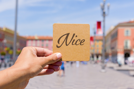 maritimes: closeup of a young caucasian man holding a brown signboard with the word Nice written in it in front of the famous Place Massena square in Nice, France