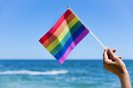 closeup of a young caucasian man waving a small rainbow flag in front of the ocean