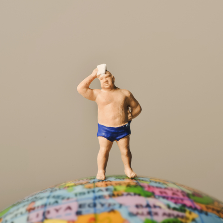 bather: a miniature man wearing swimsuit and drying his forehead with a handkerchief on the top of the terrestrial globe