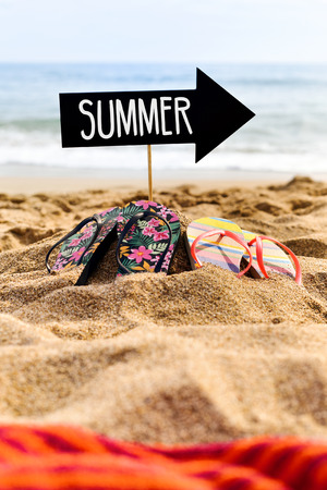 a bathing place: closeup of a black signboard in the shape of an arrow sign with the word summer written in it and two pairs of colorful flip-flops on the sand of a lonely beach