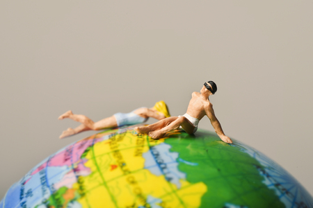 a miniature man and a miniature woman wearing both swimsuit on the top of the terrestrial globe Stock Photo