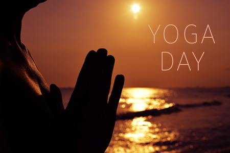 the silhouette of a young man with his hands put together as praying in front of the sea in backlight and the text yoga day