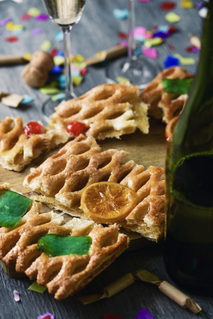 closeup of a coca de Sant Joan, a typical sweet flat cake from Catalonia, Spain, eaten on Saint Johns Eve, on a rustic table, a bottle and a pair of glasses with champagne, firecrackers and confetti
