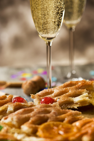 cava: closeup of a coca de Sant Joan, a typical sweet flat cake from Catalonia, Spain, eaten on Saint Johns Eve, on a rustic table, a pair of glasses with champagne, firecrackers and confetti Stock Photo