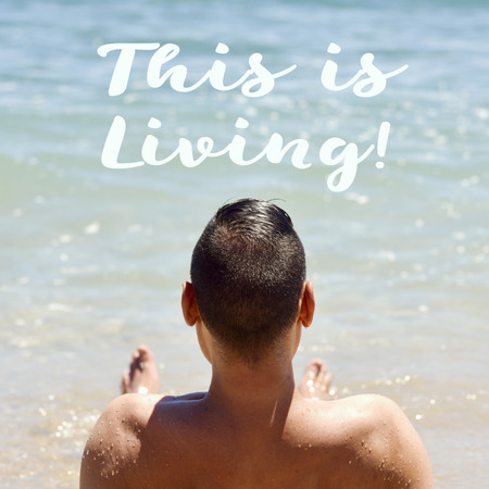 a bathing place: closeup of a young caucasian man seen from behind lying down face up on the sand in the seashore and the text this is living
