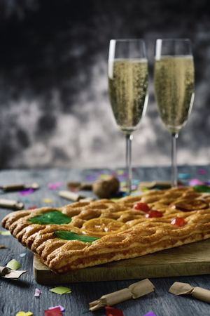 closeup of a coca de Sant Joan, a typical sweet flat cake from Catalonia, Spain, eaten on Saint Johns Eve, on a rustic table, a pair of glasses with champagne, firecrackers and confetti Stock Photo