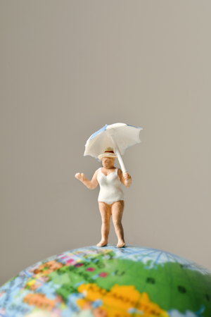 small world: a miniature old woman wearing swimsuit and holding an umbrella above her head on the top of the terrestrial globe