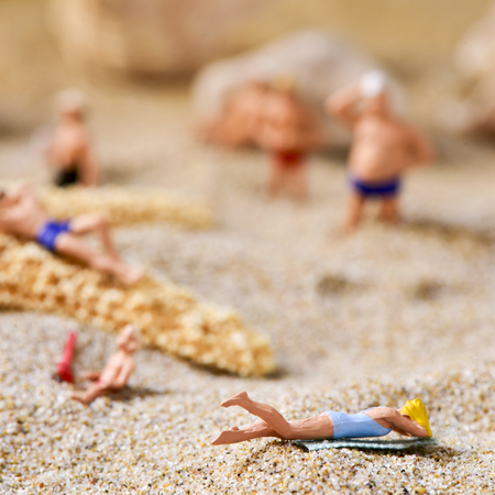 bather: some different miniature people wearing swimsuit on the sand of the beach