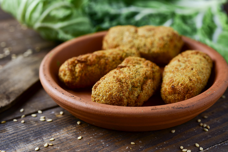 closeup of an earthenware plate with some homemade croquetas, spanish croquettes, on a rustic wooden table Reklamní fotografie - 80629805