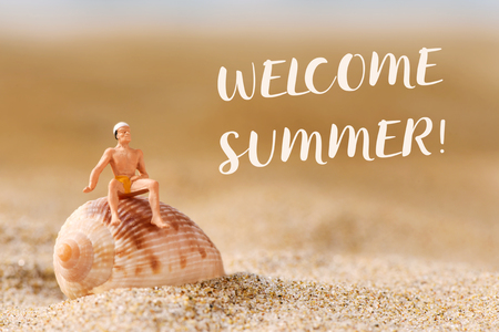 closeup of a miniature man wearing swimsuit on a seashell placed on the sand of the beach and the text welcome summer