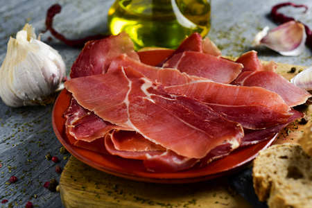closeup of an earthenware with some slices of spanish serrano ham on a wooden chopping board, and some slices of bread and a glass cruet with olive oil on a gray rustic wooden table Stock Photo