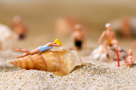 woman bath: some different miniature people wearing swimsuit relaxing on the sand of the beach