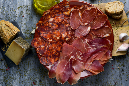 high-angle shot of a plate with an assortment of different spanish cold meats as chorizo, cured pork tenderloin and serrano ham, a piece of manchego cheese, bread and a cruet with olive oil on a table Stockfoto