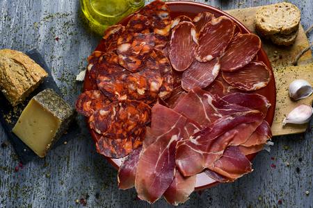 Prise de vue en grand angle d'un plat avec un assortiment de différentes viandes froides espagnoles comme le chorizo, le filet de porc cuit et le jambon serrano, un morceau de fromage manchego, du pain et un cruette à l'huile d'olive sur une table