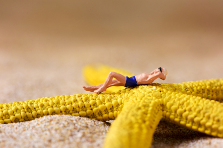 a miniature man wearing swimsuit relaxing on a yellow starfish, on the sand of the beach