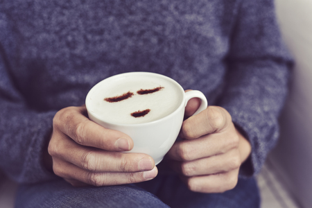 wholeness: closeup of a young caucasian man having a cup of cappuccino with a happy face drawn with cocoa powder on the milk foam Stock Photo